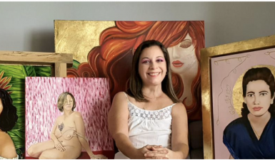 Photo of Susan Olivera sitting in front of multiple paintings, she is wearing a white t shirt, has short bob length hair, and is smiling