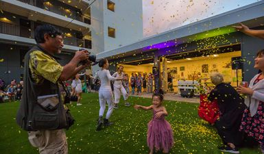 child celebrating in the sunshine being showered by flower petals